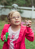 Girl playing with bubble wand in lawn