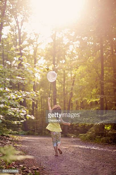Girl playing with butterfly net in forest
