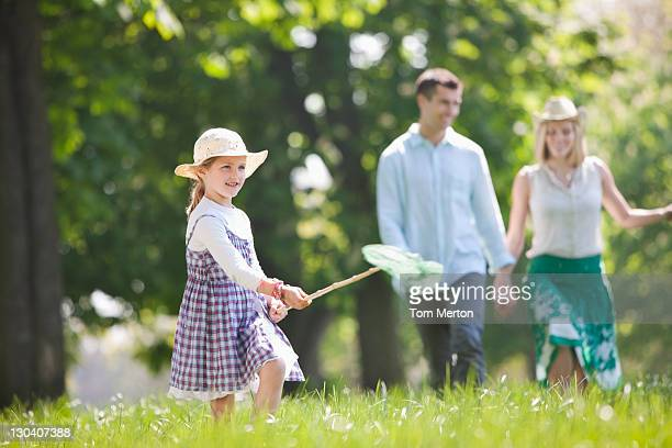 Girl playing with butterfly net in park