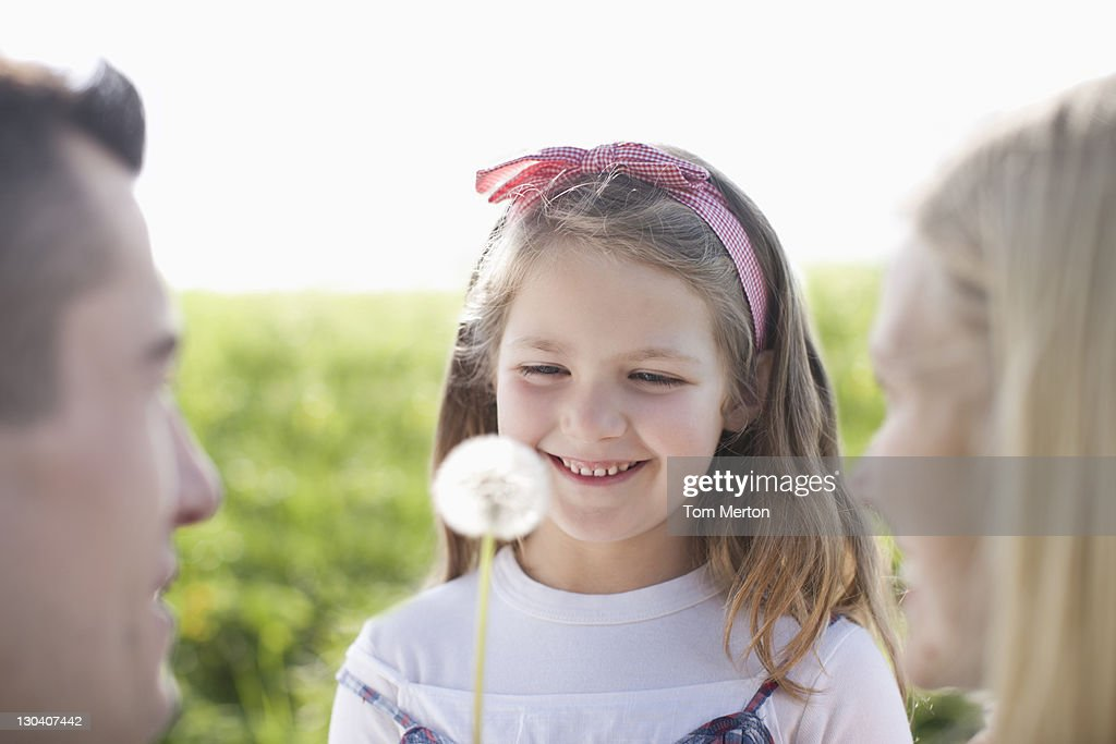 Girl playing with dandelion outdoors : Stock Photo