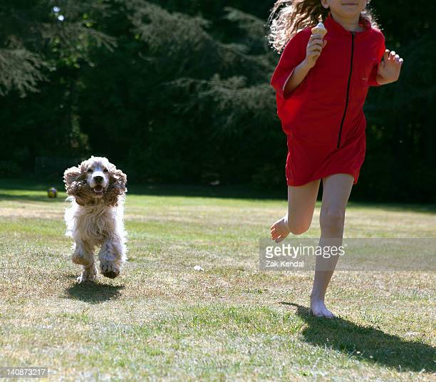 Girl playing with dog in backyard