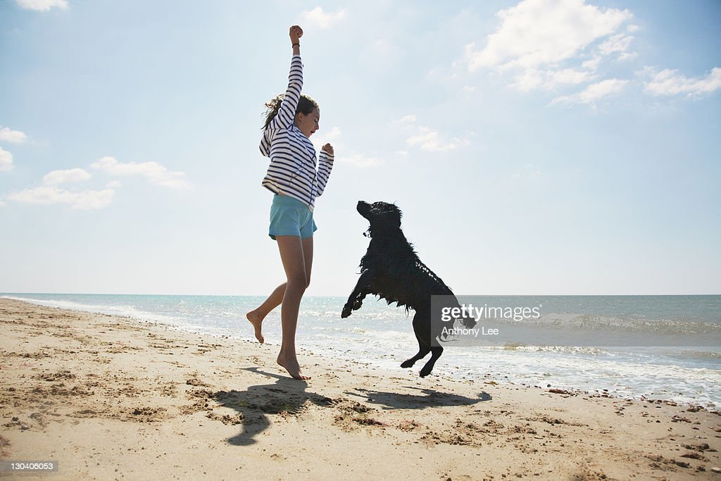 Girl playing with dog on beach : Stock Photo