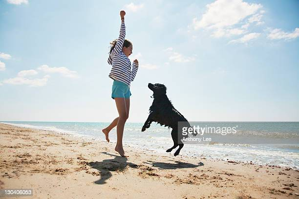 Girl playing with dog on beach