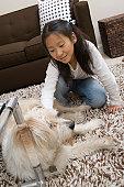 Girl (10-12) playing with dog