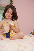 Girl (5-7) playing with doll in bedroom