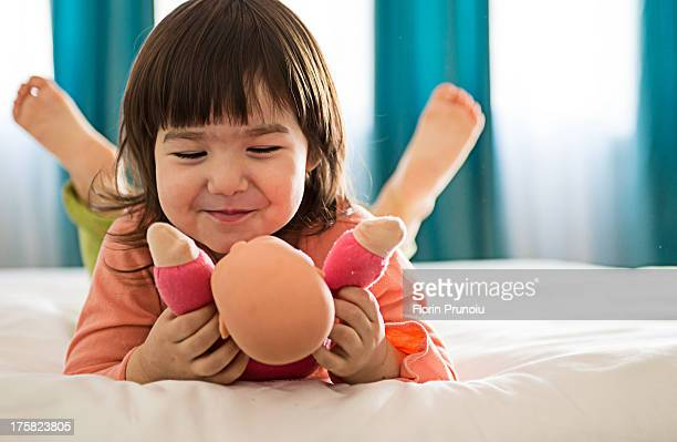 Girl playing with dolly in bedroom