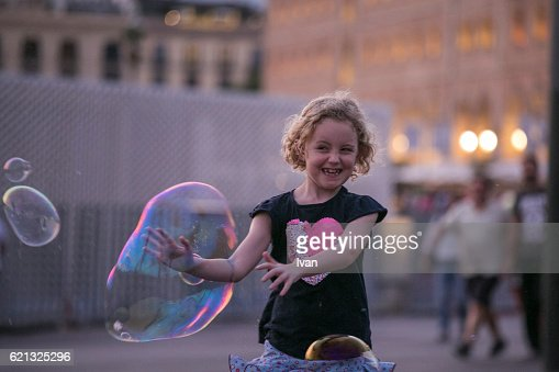Girl Playing with Giant Soap Bubbles