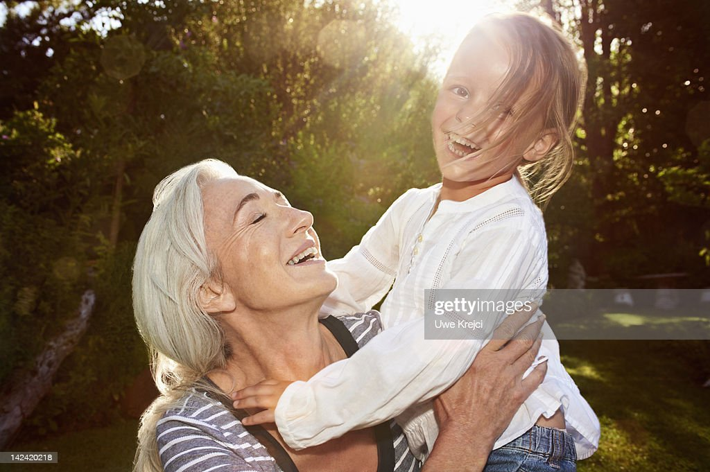 Girl playing with grandmother in the garden : Stock Photo