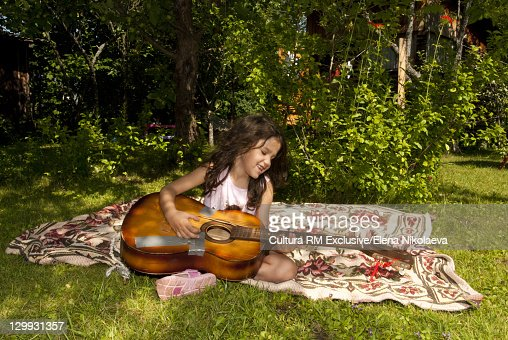 Girl playing with guitar outdoors : Stock Photo
