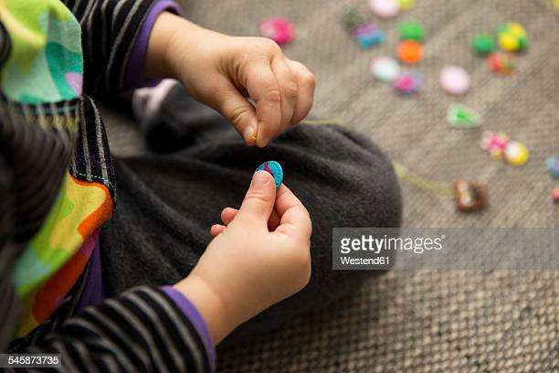 Girl playing with hand made buttons