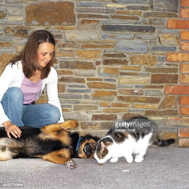 girl (13-15) playing with her dog and cat