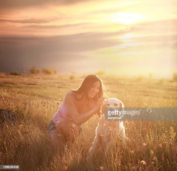 Girl playing には、自然の中の犬