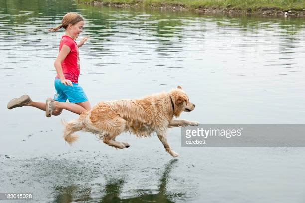 Girl playing with her dog in water