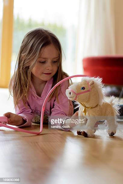 Girl playing with her toy horse