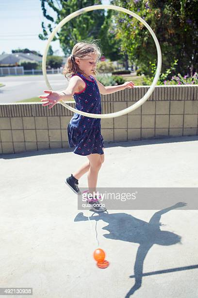 Girl playing with hula hoop and skip it