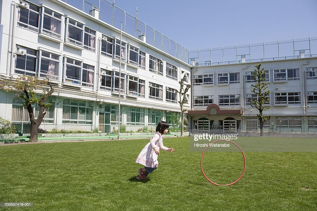 Girl (4-5) playing with hula hoop in schoolyard : Stock Photo