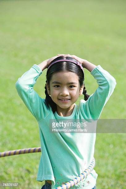Girl playing with hula hoop, smiling at camera