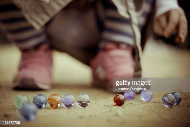 Girl playing with marbles