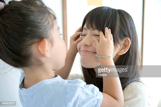 Girl playing with mother's face