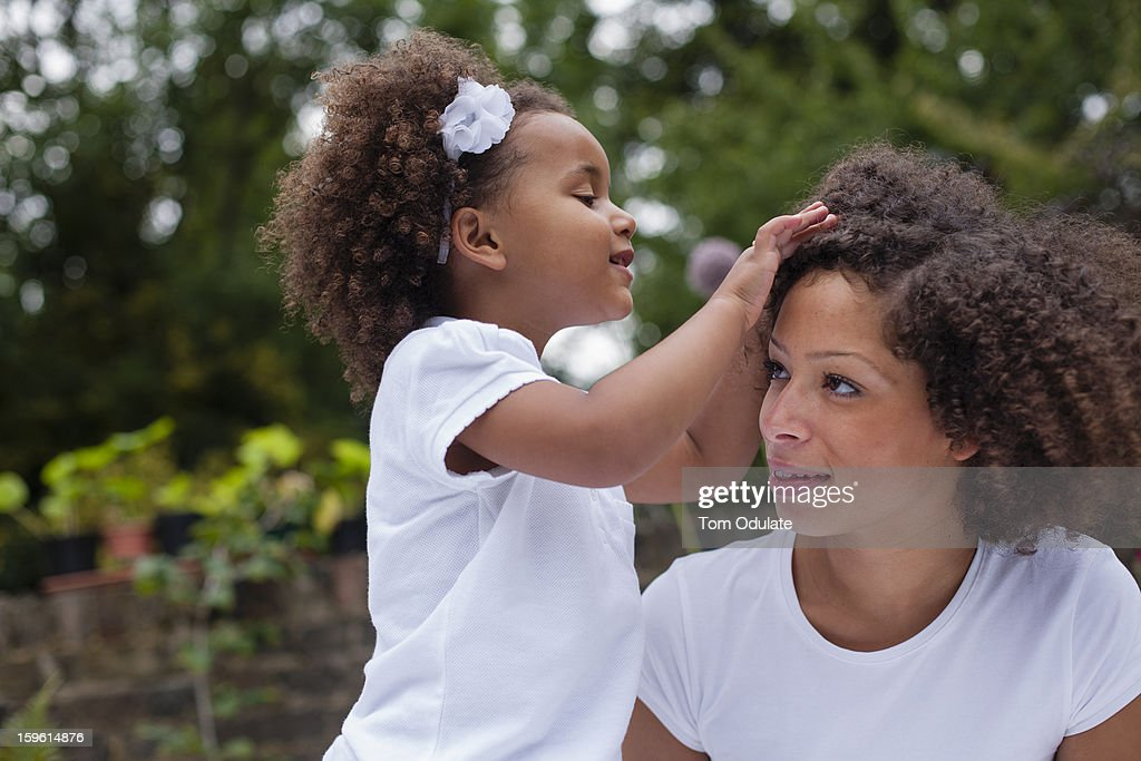 Girl playing with mothers hair outdoors : Stock Photo