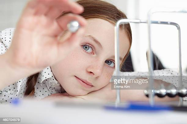 Girl playing with newton's cradle on desk