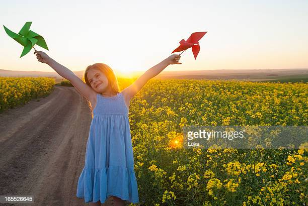 Girl playing with pinwheels outdoors