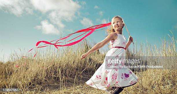 Girl playing with ribbon in long grass
