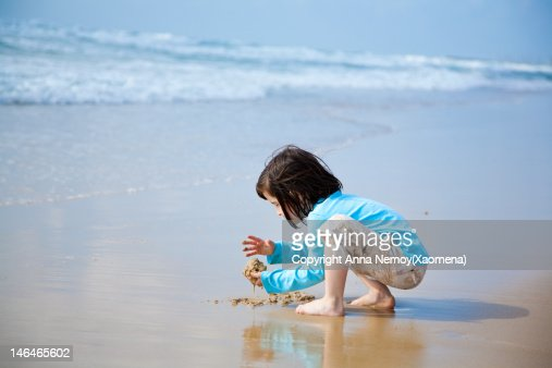 Girl playing with sand at the sea