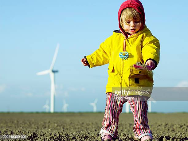 Girl (2-4) playing with sand at wind farm, low angle view