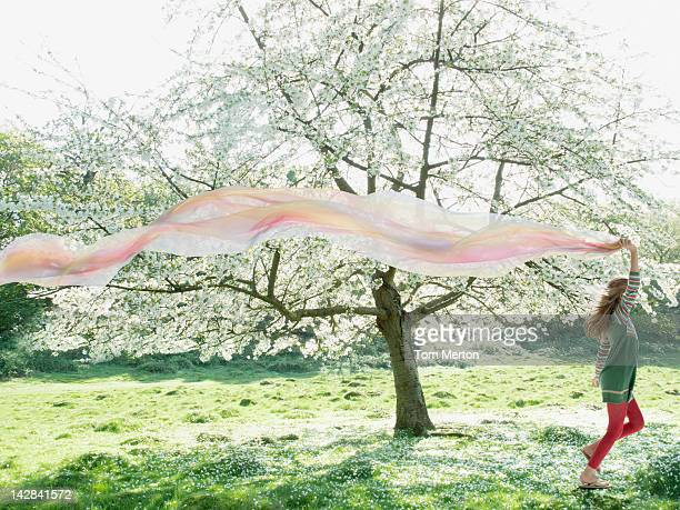 Girl playing with scarf in field