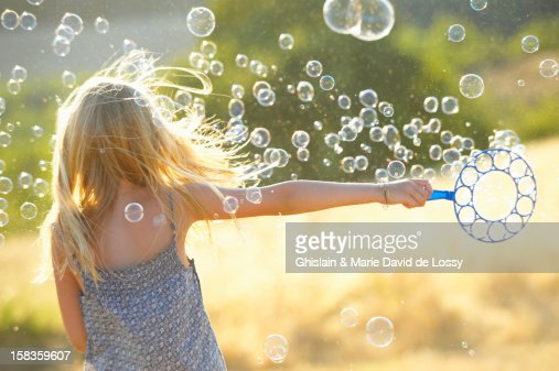 Girl playing with soap bubbles : Stock Photo