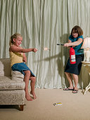 Girl (8-9) playing with sparkler in bedroom with mother lurking with fire extinguisher