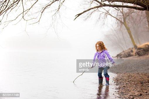 女の子 と遊ぶスティック川の朝の霧の