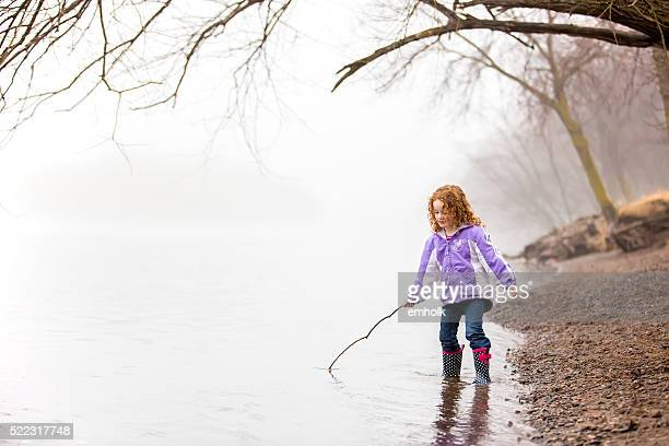 Girl Playing With Stick in River on Foggy Morning