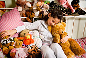 Girl playing with stuffed toys and smiling in a bedroom