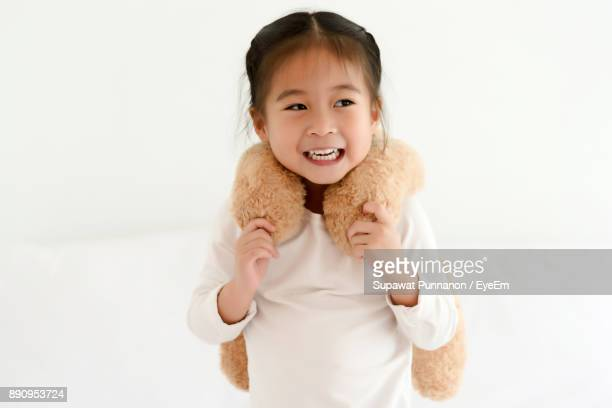 Girl Playing With Teddy Bear Against White Wall At Home