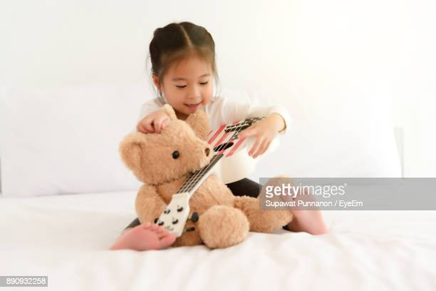 Girl Playing With Teddy Bear And Guitar On Bed At Home