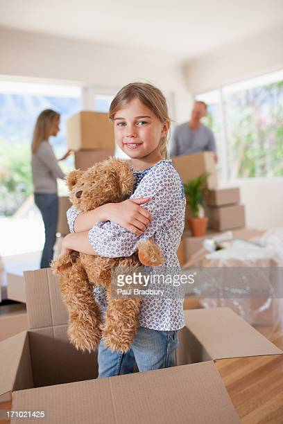 Girl playing with teddy bear in box in new house