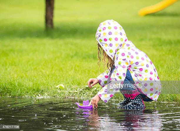 Girl Playing With Toy Boat in Rain Puddle