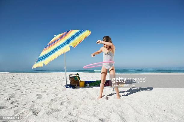 Girl (7-9) playing with toy hoop on beach