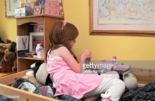 Girl playing with toys in bedroom : Stock Photo