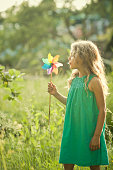 Girl playing with windmill in garden