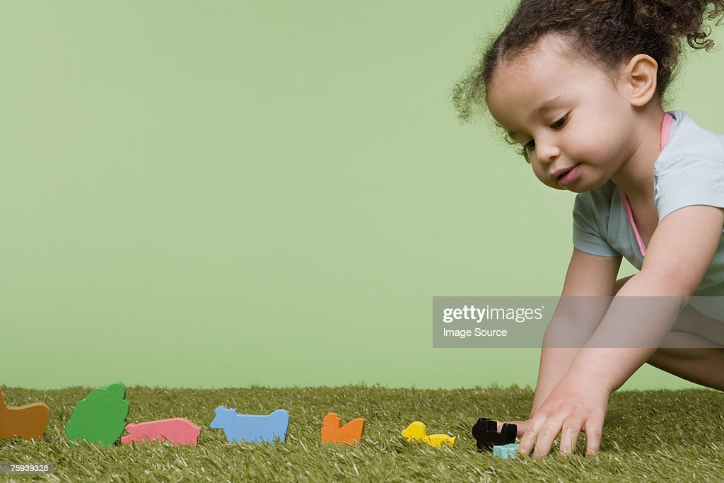 Girl playing with wooden animals : Stock Photo