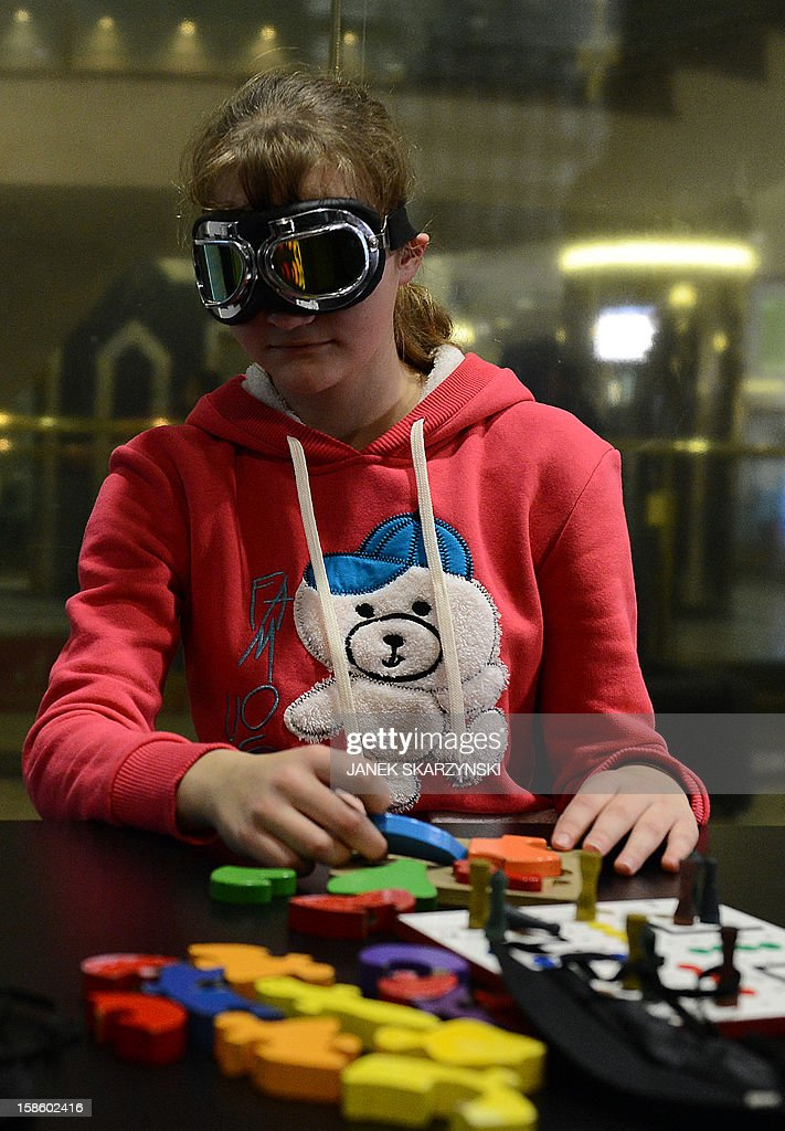 A girl plays a game that stimulates the visitors' senses and reveals the tools that the blind use in their daily lifes in the 'invisible exhibition' on December 18, 2012 in Warsaw.