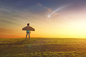 Little girl plays astronaut. Child on the background of sunset sky. Kid is looking at falling star and dreaming of becoming a spaceman.