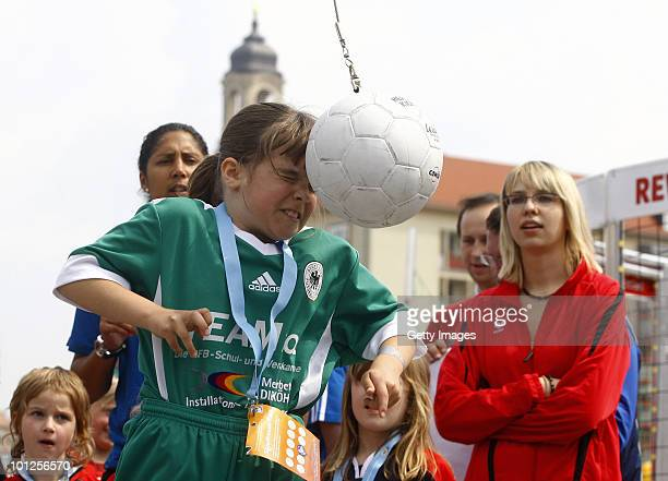 A girl plays football next to Steffi Jones head of the Organising Committee of the FIFA Women's World Cup 2011 during the FIFA U20 Women's World Cup...
