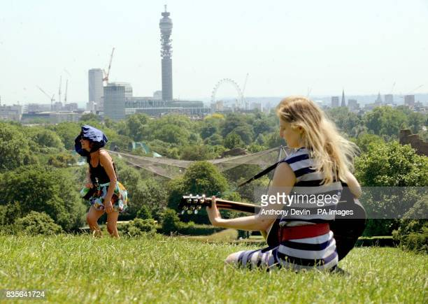 A girl plays guitar as people enjoy the sunshine on Primrose Hill London