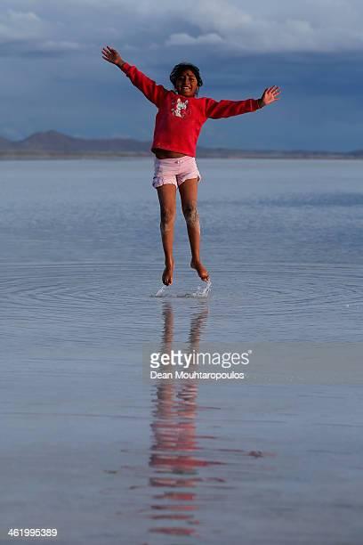 A girl plays in the salt water at the Salar de Uyuni or Uyuni Salt Flat during Day 7 of the 2014 Dakar Rally on January 11 2014 in Uyuni Bolivia