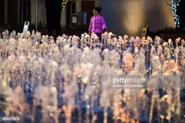 A girl plays near a water fountain in Shanghai on December 10 2017 / AFP PHOTO / CHANDAN KHANNA