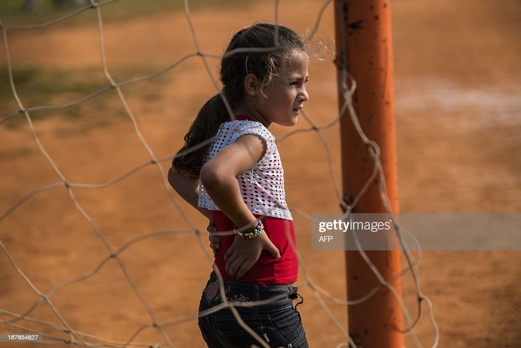 A girl plays near the Itaquerao Stadium (Corinthians Arena) in Sao Paulo, Brazil on May 1, 2013. The stadium has been completed 70 % of the process and will host the opening match of FIFA World Cup 2014. AFP PHOTO/Yasuyoshi CHIBA